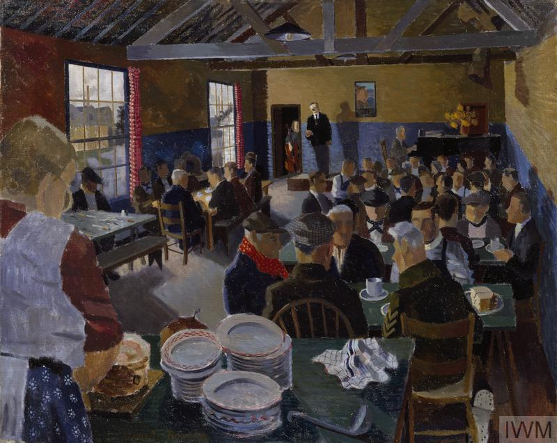 The interior of a large room, filled with people seated around tables.  In the foreground there is a table stacked with plates, behind which stands a woman wearing an apron.